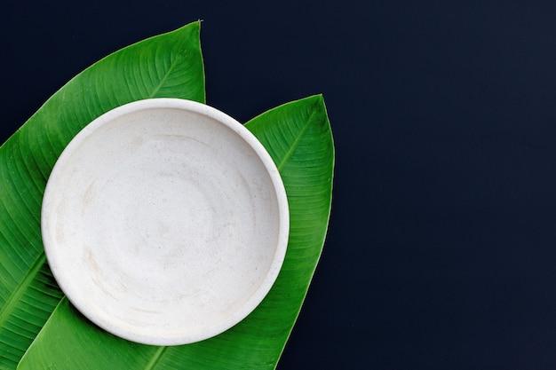 Leere weiße platte auf tropischen bananenblättern