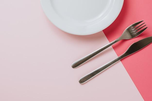 Leere weiße platte mit besteck auf einem rosa hintergrund.