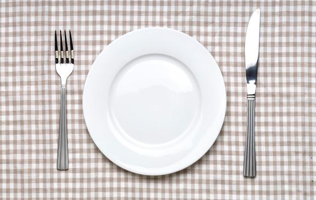 Leere weiße platte mit gabel und messer auf karierter gingham-tischdecke