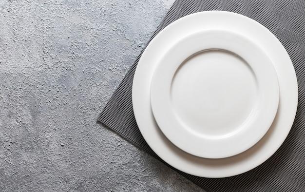Leere weiße platte serviert auf reliefserviette und geprägtem grauem betonhintergrund. draufsicht modell für menü