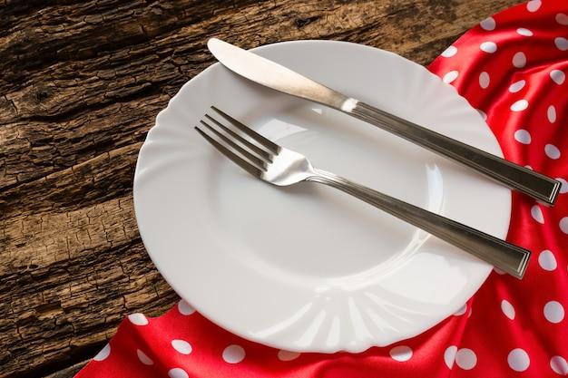 Leere weiße platte und tischbesteck auf roter serviette