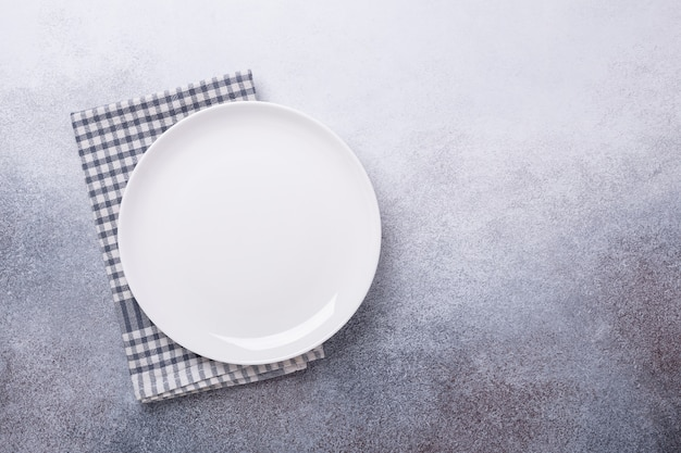 Leere weiße platten- und leinenserviette auf steinhintergrund
