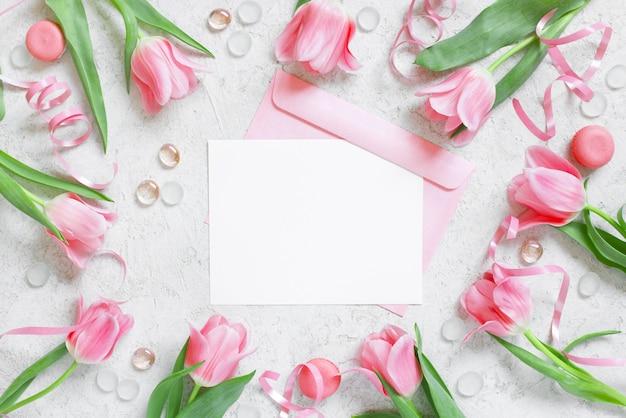 Leere weiße postkarte mit umschlag und rahmen von tulpen
