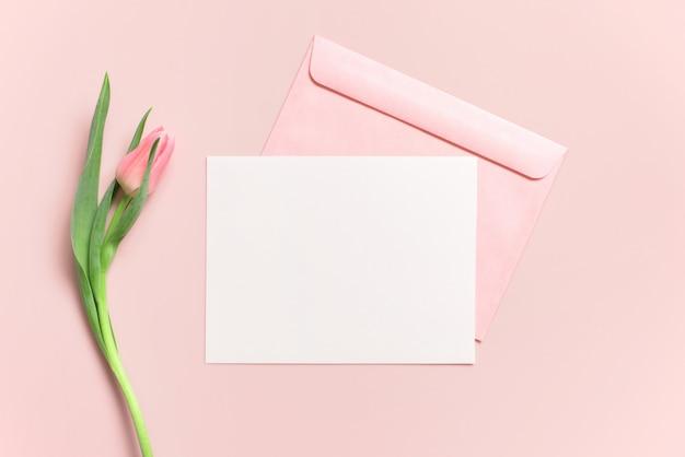 Leere weiße postkarte oder karte mit umschlag und tulpe