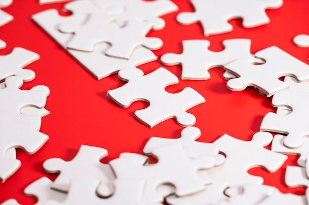 Leere weiße puzzleteile auf flachem dof des roten hintergrunds