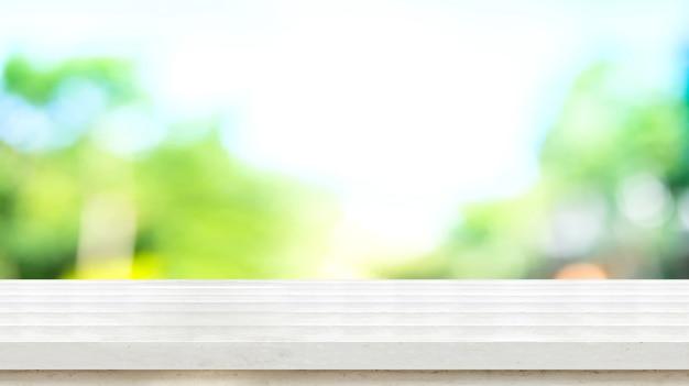 Leere weiße rustikale hölzerne tischplatte mit baum bokeh des blauen grüns der unschärfe