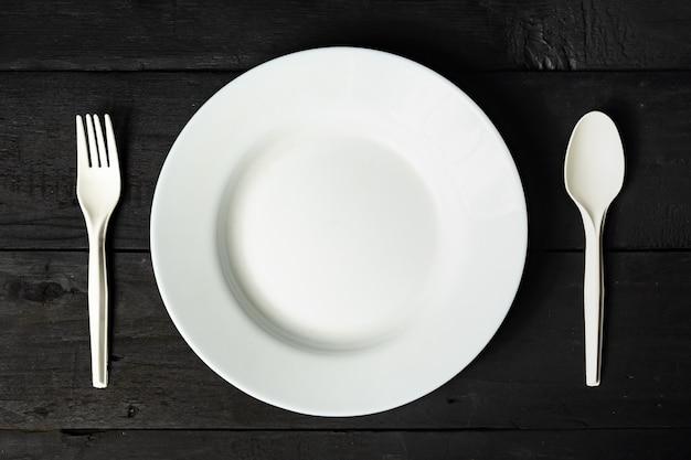 Leere weiße schüssel, gabel und löffel auf schwarzer hölzerner tabelle, großaufnahme. diätkonzept: flache lage von sauberen küchentellern auf dunkler rustikaler oberfläche