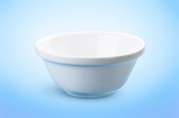Leere weiße schüssel lokalisiert auf dem blau, ideal für die darstellung von milchprodukten