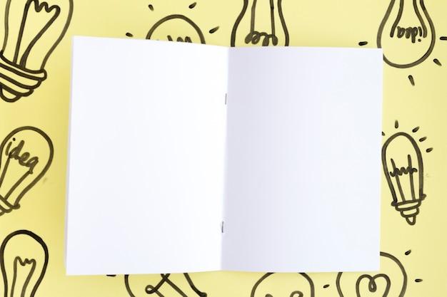 Leere weiße seite an hand gezeichneter glühlampe über dem gelben hintergrund