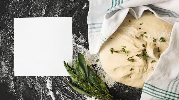 Leere weiße seite und roher teig mit rosmarin auf küchenarbeitsplatte