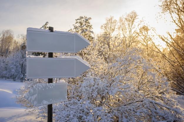 Leere weiße spurzeiger, wegweiser im sonnenlicht gegen winternatur