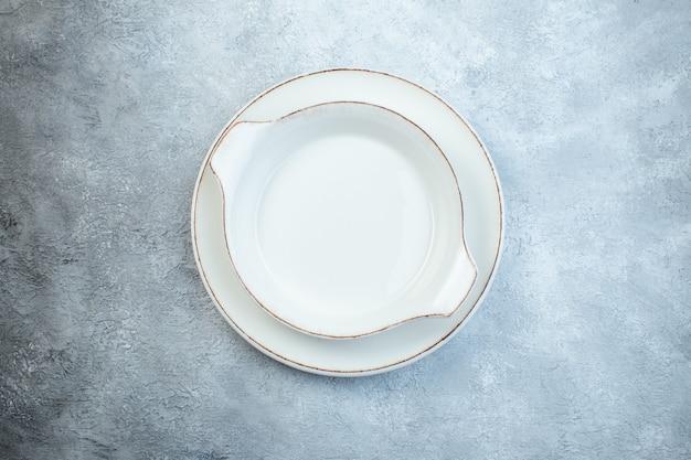 Leere weiße suppenteller auf grauer oberfläche mit beunruhigter oberfläche mit freiem platz