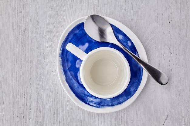 Leere weiße tasse für heiße getränke mit einem löffel auf einem blauen teller auf einem weißen holztisch draufsicht