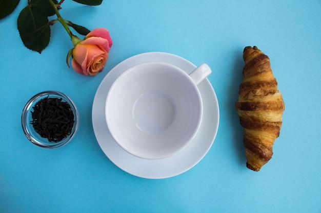 Leere weiße tasse für tee, croissant, schwarzen tee und rosa rose