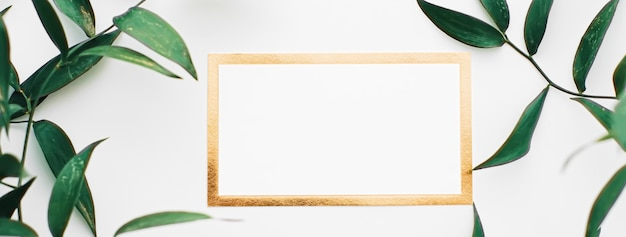 Leere weiße und goldene karte grüne blätter auf weißem hintergrund als botanischer rahmen flatlay hochzeitseinladung ...