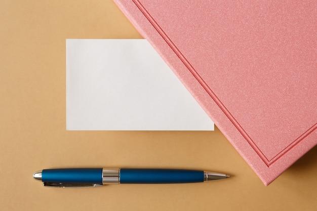 Leere weiße visitenkarte, rosa tagebuch und metallisch blauer stift auf brauner flacher lage