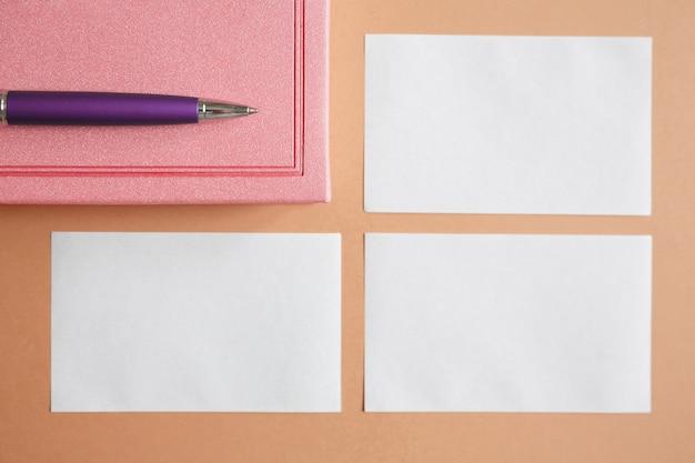 Leere weiße visitenkarte, rosa tagebuch und metallischer lila stift auf braun