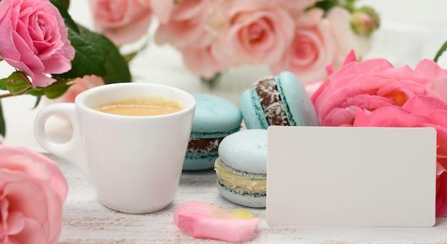 Leere weiße visitenkarte und tasse mit espresso-kaffee und weiße keramiktasse mit kaffee und blauem macaron auf einem weißen tisch, hinter einem strauß rosa rosen