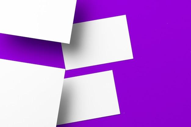 Leere weiße visitenkarten auf draufsicht des lila hintergrunds