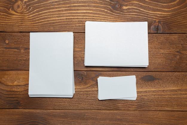 Leere weiße visitenkarten auf hölzerner tabelle