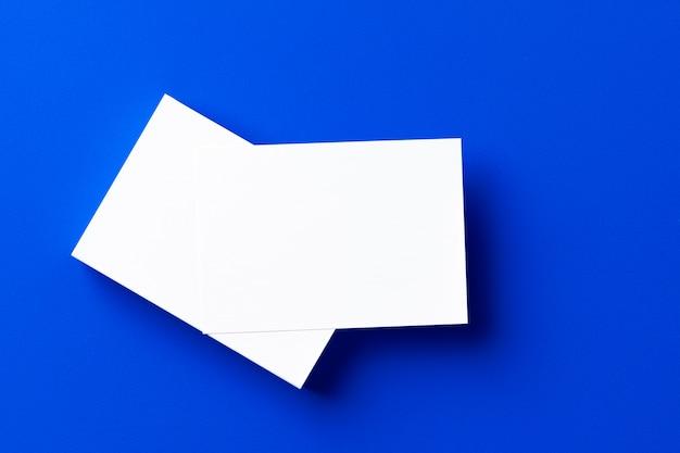 Leere weiße visitenkarten auf klassischem blau