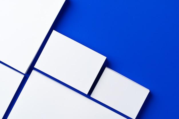 Leere weiße visitenkarten auf klassischem blauem hintergrund