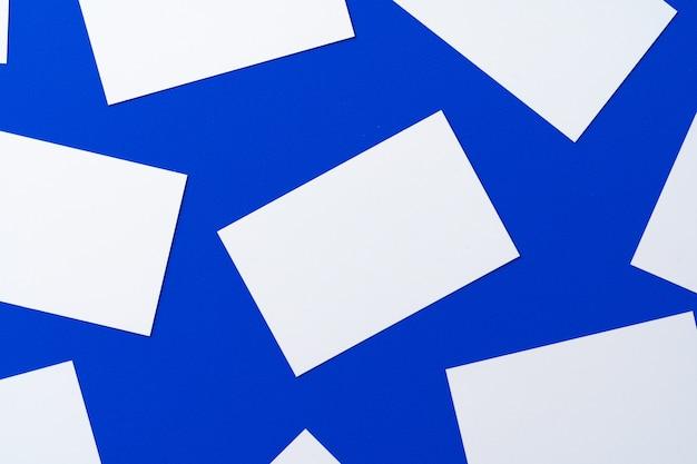 Leere weiße visitenkarten auf klassischer blauer wand