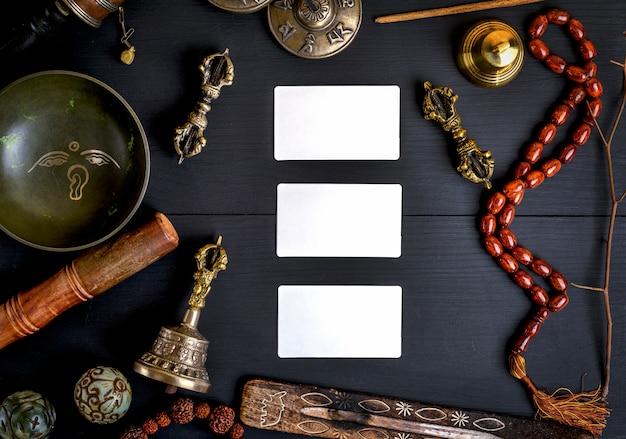Leere weiße visitenkarten inmitten asiatischer religiöser gegenstände