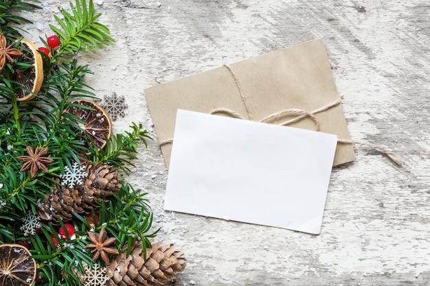 Leere weiße weihnachtsgrußkarte und umschlag mit tannenzweigen, nahrungsmitteldekorationen und tannenzapfen