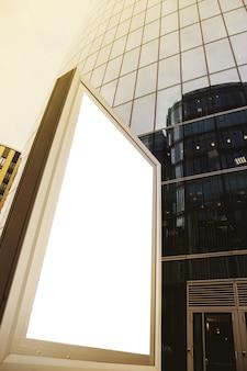 Leere werbetafel auf der vorderseite des geschäftsgebäudes. banner auf dem hintergrund des wolkenkratzers ist im modernen stil gestaltet. architektur des gebäudes im geschäftsviertel der metropole. urheberrechtsraum