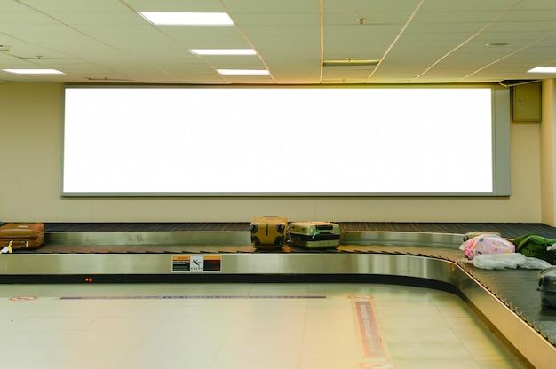 Leere werbungsanschlagtafel an der gepäckausgabe im flughafen