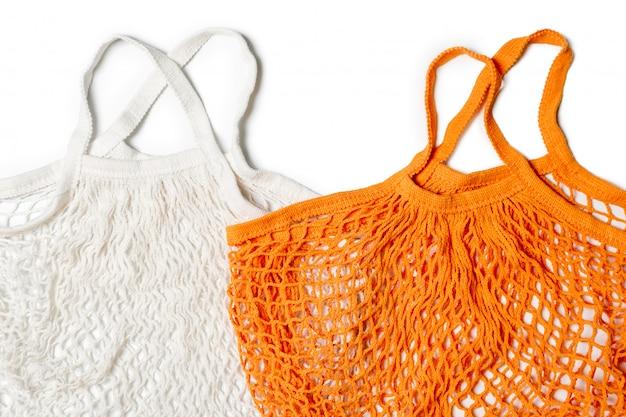 Leere wiederverwendbare baumwoll-einkaufsschnur-taschen auf weißem hintergrund. umweltfreundliche netzbeutel oder käufer. ablehnung von kunststoff, abfallfreiheit, recycling und wiederverwendung.