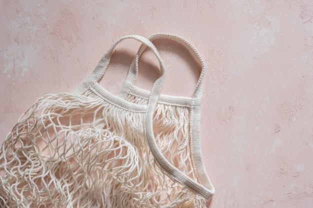 Leere wiederverwendbare einkaufstasche auf rosa. null-abfall-konzept.