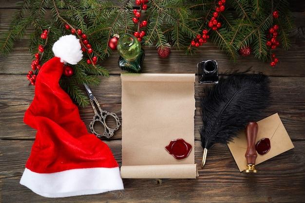 Leere wunschliste für den weihnachtsmann auf holztisch mit weihnachtsschmuck. draufsicht.