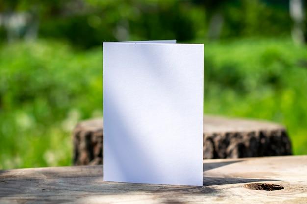 Leere zweifache weiße karte, die auf holzschreibtisch im freien mit blumenschatten und unscharfem naturhintergrund steht