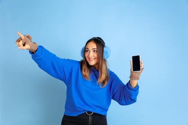 Leeren bildschirm anzeigen. porträt der kaukasischen frau auf blauem raum. schönes weibliches modell in warmer kleidung