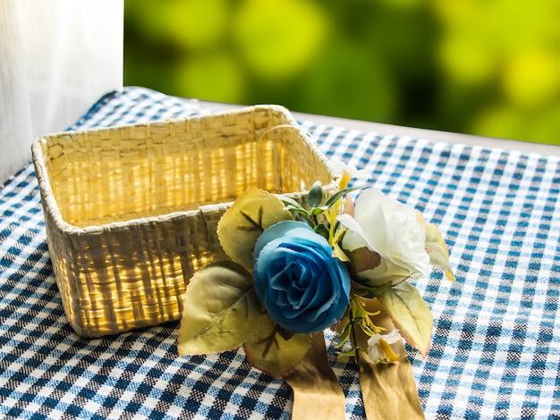 Leeren korb und blumenstrauß aus stoff auf einem tisch in der nähe des fensters.