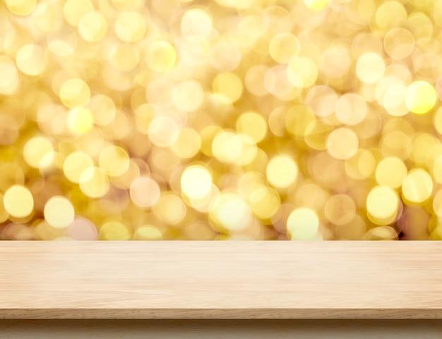 Leeren sie beige hölzerne tischplatte mit abstraktem hintergrundgold-bokeh licht