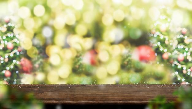 Leeren sie braune hölzerne tischplatte mit abstraktem unschärfenweihnachtsbaum-dekorball und -schnee