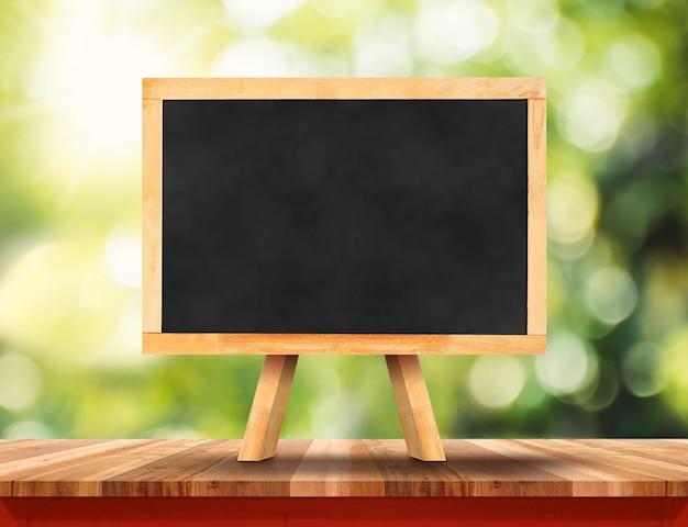 Leeren sie braune hölzerne tischplatte mit sonne und verwischen sie grünen baum bokeh hintergrund