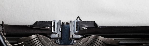 Leeren sie ein blatt papier für ihren text, das in eine schreibmaschine eingefügt wurde.
