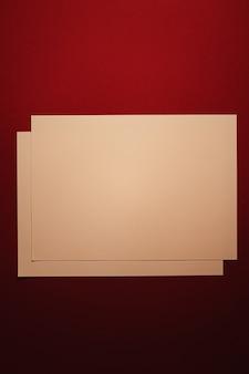 Leeren sie ein papier beige auf dunkelrotem hintergrund als büromaterial flach, luxus-branding flach und...