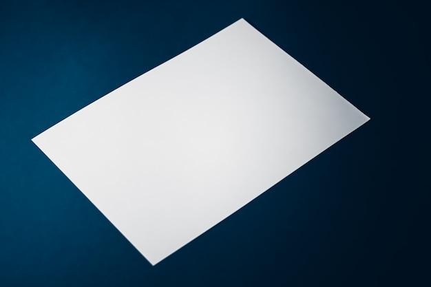 Leeren sie ein weißes papier auf blauem hintergrund als büromaterial flach, luxus-branding flach und bh ...