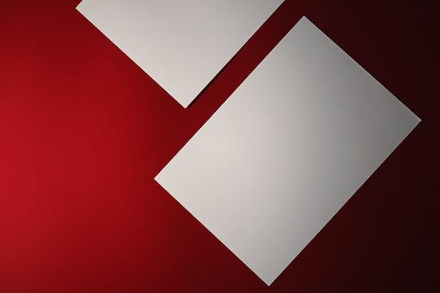 Leeren sie ein weißes papier auf rotem hintergrund als büropapier flach, luxus-branding-flach und markenidentitätsdesign für mockup