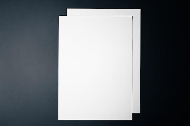Leeren sie ein weißes papier auf schwarzem hintergrund als büromaterial flach, luxus-branding flach und ...