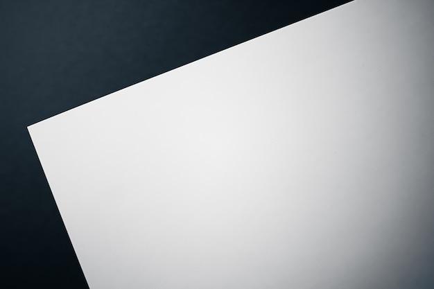 Leeren sie ein weißes papier auf schwarzem hintergrund als büropapier flach, luxus-branding-flach und markenidentitätsdesign für mockup