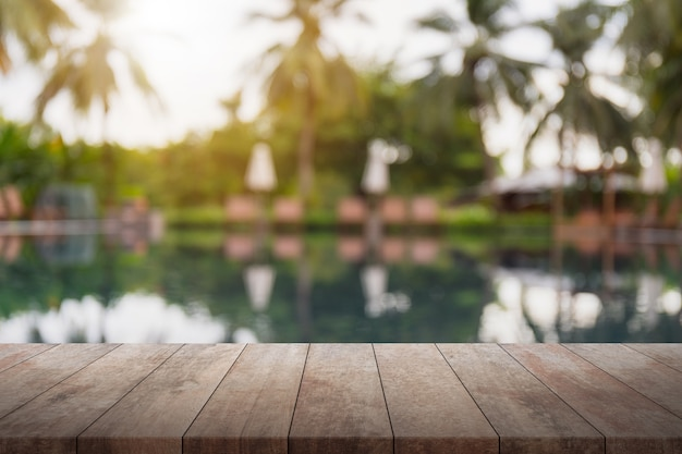 Leeren sie hölzerne tischplatte und unscharfen swimmingpool im tropischen rücksortierunghintergrund.