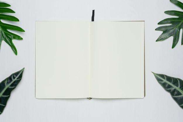 Leeren sie offene notizbuchseite auf weißem hölzernem hintergrundbüroschreibtisch
