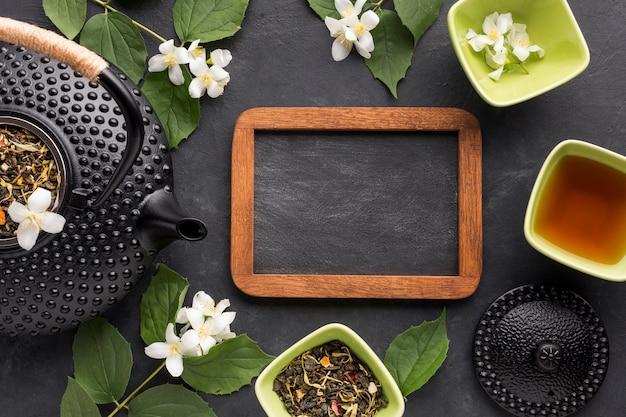 Leeren sie schiefer mit getrockneten kräutern und weißer jasminblume auf schwarzem hintergrund