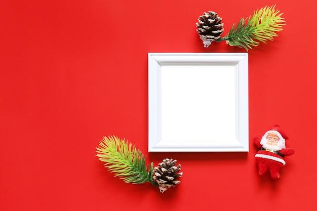 Leeren sie schwarzen fotorahmen und weihnachtsdekoration auf rotem hintergrund.